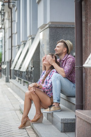 closing eyes: Cheerful smiling young couple having fun outside. Young man in straw hat closing eyes of his girl-friend. Stock Photo