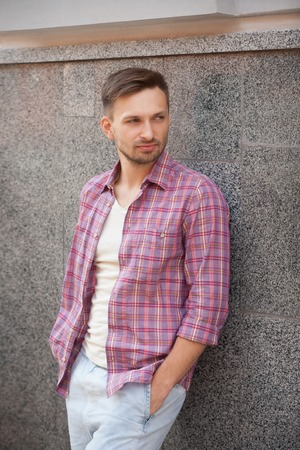Portrait of young man with his hands in pockets. Manin plaid shirt seriously posing near concrete wall.