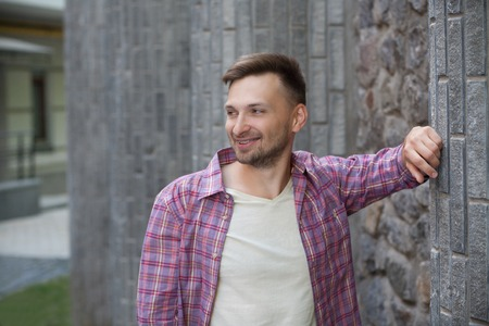 manin: Young man smiling near brick wall. Manin plaid shirt posing for photographer and looking somewhere right. Stock Photo