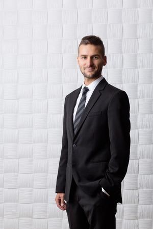 traje sastre: Joven apuesto hombre de negocios sonriendo para la c�mara. Hombre alto de pelo corto en traje de negocios negro manteniendo su mano en el bolsillo.