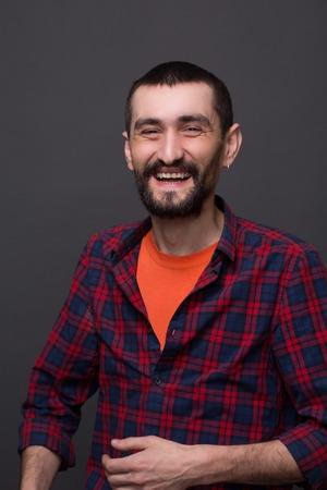 chemise carreaux: Close-up portrait de hippie barbu sur gris fonc�. L'homme en chemise � carreaux et T-shirt riant et montrant ses dents.