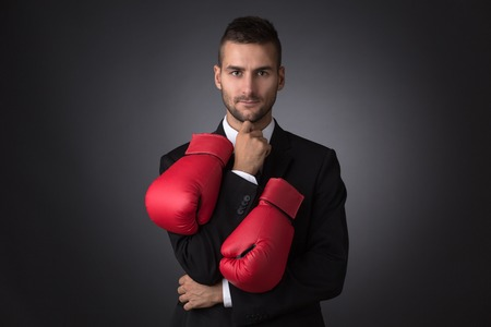 short haircut: Businessman ready to fight with boxing gloves over grey background. Man with short haircut looking at the camera.