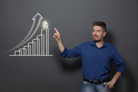 concerning: Handsome business man in casual clothes. Smiling man pointing out the diagram concerning profit business strategy on dark grey background.