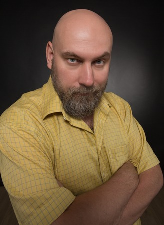 Portrait of serious and strict bearded man on black. Bold man in yellow shirt posing with his arms crossed.