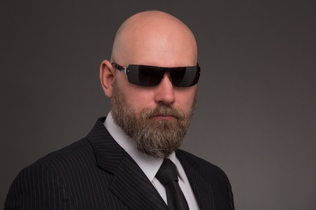 demanding: Hipster bearded man poising in black sunglasses. Bold man in business suit looking so serious and demanding on dark grey. Stock Photo