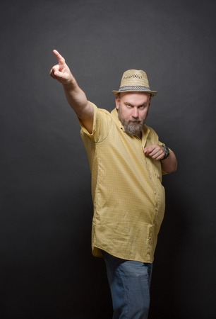 annoyance: Serious bearded man pointing out on black background. Bold man in straw hat frowning, because of annoyance.