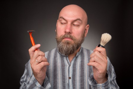 jailbird: Bold jailbird sitting in the prison isolated on dark grey. Bearded man keeping razor and brush, he is going to shave. Stock Photo