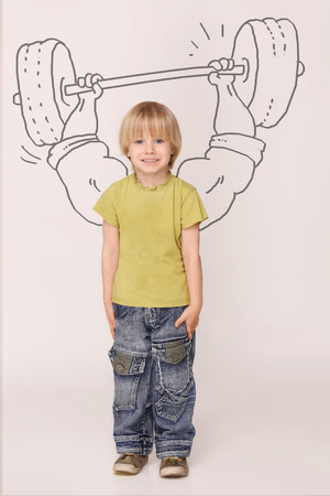 Handsome little boy dreaming about huge muscles. Boy with blond hair in yellow T-shirt and jeans lifting 100 kilos barbell. Stock Photo