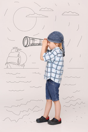 imagining: Portrait of little man playing like pirate. Boy in navy blue do-rag imagining that he is looking through tube in the ships in the sea.