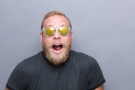 Portrait of astonished bearded man on grey. Man with short blond hair opened his mouth because of being surprised by smth. Stock Photo