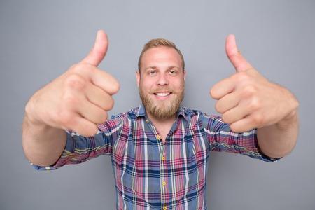 hombre barba: Hombre barbudo sonriente que muestra el pulgar dos planos. hombre feliz en azul marino, camisa a cuadros roja satisfacer su estilo de vida en el fondo gris. Foto de archivo