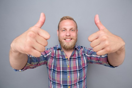 Smiling bearded man showing two thumb-ups. Happy man in navy blue, red plaid shirt satisfying his lifestyle on grey background.