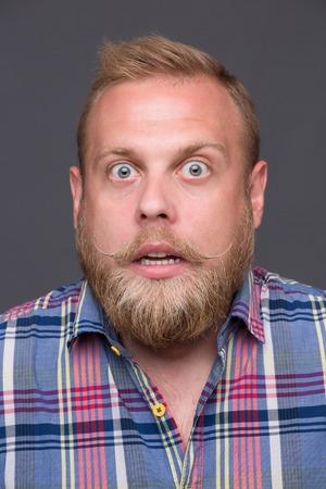 chemise carreaux: Profil des �tonn� homme barbu sur gris fonc�. Tr�s surpris homme blond aux cheveux courts en chemise � carreaux sur �coute ses yeux.
