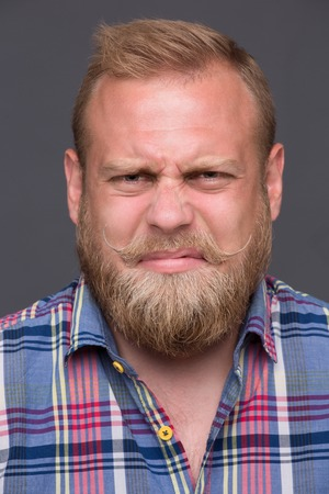 discontented: Profile of discontented bearded man on dark grey. Short-haired blond man in plaid shirt frowning disgust because of bad mood. Stock Photo