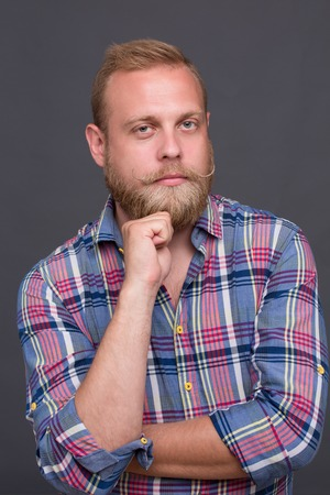 plaid shirt: Portrait of handsome serious bearded man. Blond man in fashionable plaid shirt keeping his chin and posing for photographer.