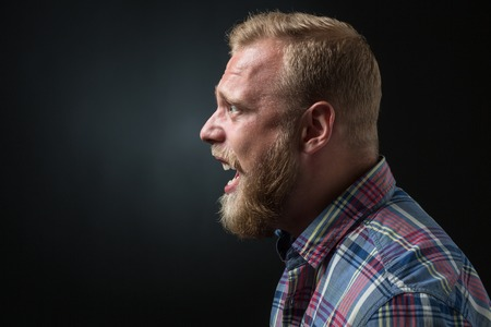 blond hair: Profile of shouting bearded man isolated on black. Blond man in plaid shirt screaming because of annoyance.
