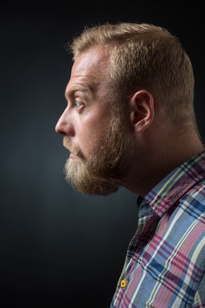 demanding: Profile of demanding bearded man on black background. Short-haired blond man googling his eyes. Stock Photo