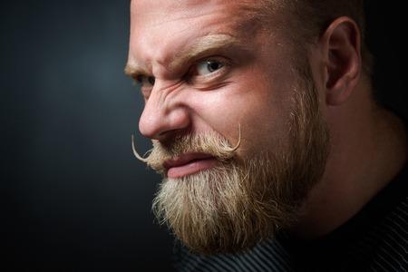 hombre con barba: Perfil del hombre barbudo aterradora en negro. Hombre con mirada seria mirando con maldad y entrecerrando los ojos.