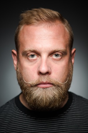 apathetic: Portrait of serious bearded man on balck. Blond man looking straight, because he is apathetic person. Stock Photo