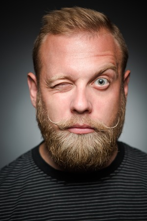 apathetic: Portrait of bearded man with his right eye closed. Blond man in black T-shirt looking so serious on black background.
