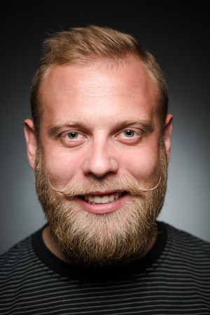 satisfying: Photo of bearded man showing his teeth on black. Happy man satisfying his photosession in studio.