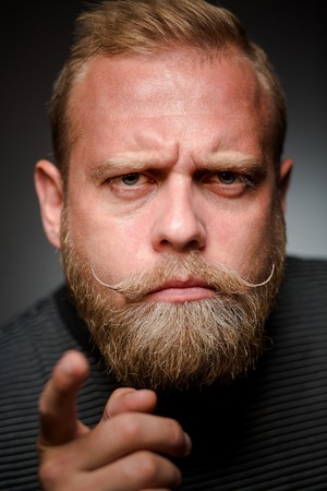 apathetic: Portrait of tough bearded guy on black background. Short-haired blond man having a bone to pick with someone.
