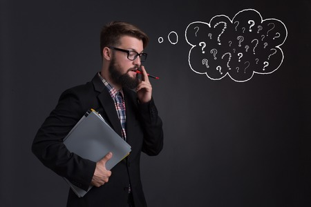 gaze: Hipster bearded businessman talking over mobile phone with partners. Man in glasses at gaze, because he doesnt know what to answer. Stock Photo