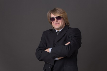 traje sastre: Hombre de negocios feliz en gafas de sol aislado en gris oscuro. Hermoso hombre en traje de negocios negro posando con los brazos cruzados.