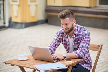 Photo of a thoughtful young man communicating with friends using Skype on laptop. Bearded man in earphones enjoyimg time in the cafe with cup of coffee.