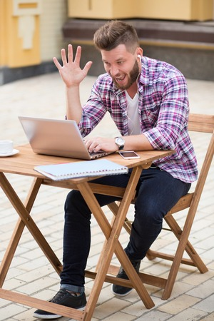 skype: Smiling hipster man communicating with his foreign friends using Skype. Bearded man sitting in the cafe with laptop and waving with his hand. Stock Photo