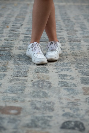 jogging shoes: Close-up picture of womans legs in white sneakers outdoors. Woman demonstrating her expensive jogging shoes. Stock Photo