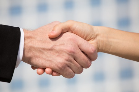 promising: Two businesspeople shaking hands, business concept. Businessman and businesswoman making promising business deal. Stock Photo