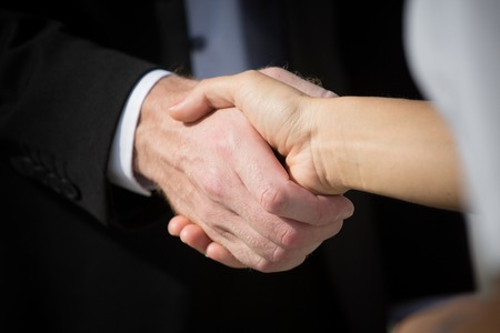 Business handshake and business people. Business handshake for closing the deal after singing the lucrative contract between companies. Stock Photo