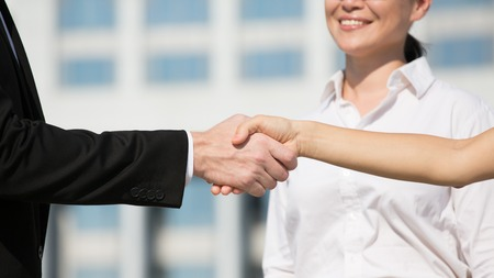lucrative: Handshake with businesswoman at backdrop showing business partnership. Man and woman have singed lucrative contract. Stock Photo