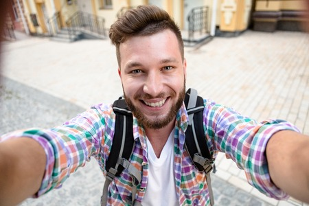 Smiling tourist with backpack making selfies isolated on beautiful modern buildings located in the city centre. Man happy spending his daytime.