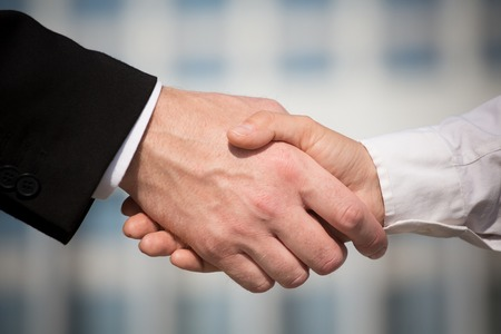 Business handshake on bright background. Photo of handshake of business partners after signing promising contract. Stock Photo
