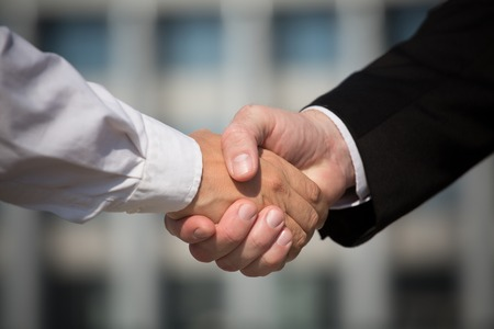 black handshake: Business handshake, the deal is finalized between two enterprises. Man in black suit and woman in white one have signed the agreement. Stock Photo