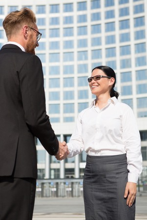 promising: Smiling and confident businesswoman in sunglasses slaking hand to her partner businessman. They have singed promising agreement.