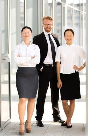 tall man: Close-up picture of business people in full length. Tall man in glasses posing with his hands in pockets, businesswomen smiling. Stock Photo