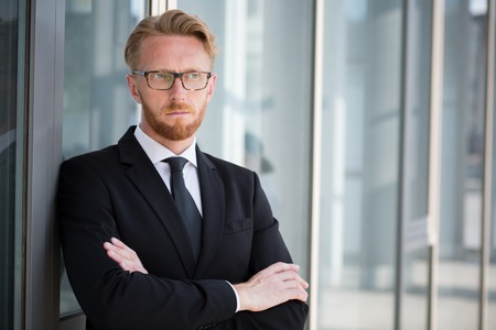 human arm: Portrait of serious businessman with folded arms posing near glass window. Blond handsome man in glasses looking away. Stock Photo