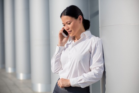buiding: Asian young businesswoman using cell phone near office buiding. Woman in white shirt speaking with her partners.