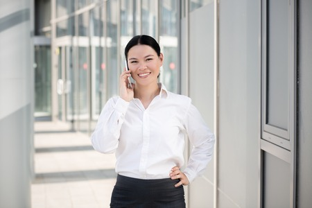 businesswoman skirt: Portrait of confident businesswoman speaking on the phone. Young asian businesswoman in white shirt and black skirt holding one hand on hip and smiling.