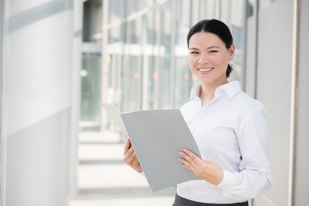 mujer trabajadora: Portrait of confident businesswoman. Attractive young businesswoman holding documents and smiling for the camera.