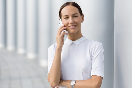 expected: Young businesswoman talking over cell phone. Smiling lady in white shirt discussing important business ideas and expected profit. Stock Photo