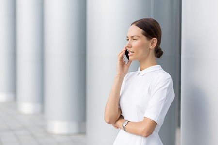 white suit: Confident young businesswoman keeping arms crossed and looking away while standing against white column. She is speaking over phone.