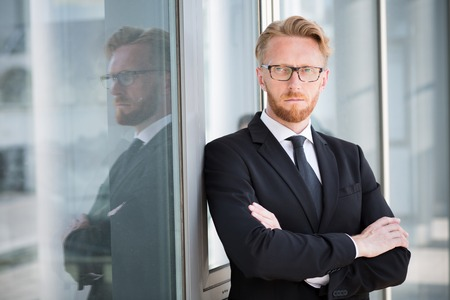 arm: Profile of serious businessman in glasses and suit. Successful businessman standing with his arms folded against glass French window.