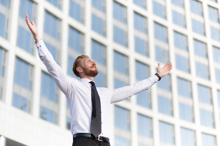 Businessman rejoicing for his success. Red-haired man in white shirt and tie looking at the sky and happy celebrating his victory. Stock Photo