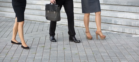 hark: Close-up picture of peoples legs. Low section of businesspeople walking along the office building after hark work. Stock Photo