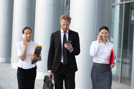 suit: Businesswomen using cell phones while walking on path outside office. Man in black busines suit with brief case going to call to his secretary. Stock Photo