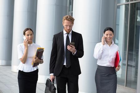 traje formal: Empresarias que usan tel�fonos celulares mientras recorren en el camino fuera de la oficina. Hombre en busines traje negro con malet�n va a llamar a su secretaria.